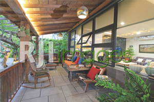 Area teras rumah dengan unsur kayu & batu alam yang mendominasi