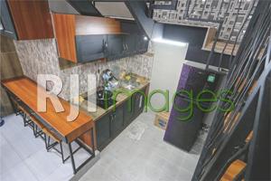 Dapur lantai bawah bernuansa industrial sebagai fasilitas bersama