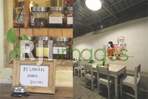 Toples kopi tertata rapi di sudut bar dan garasi sebagai area makan